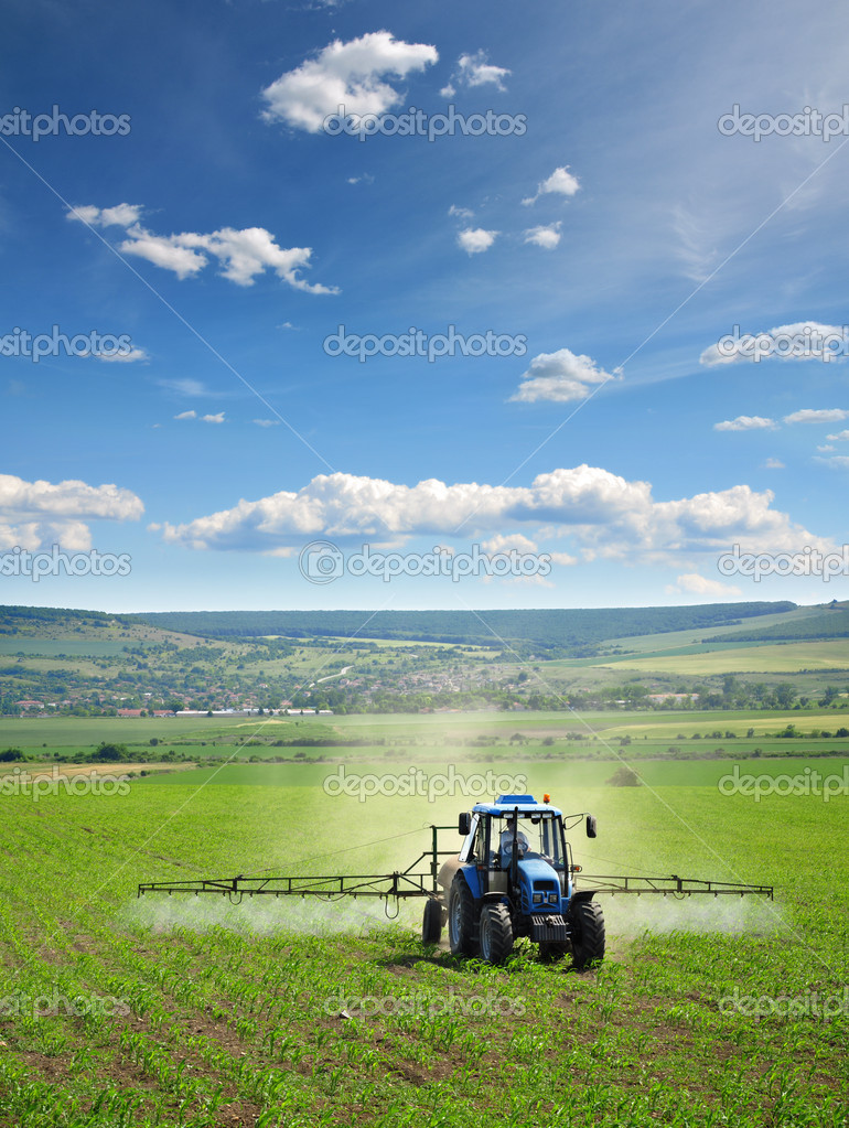 Farming tractor plowing and spraying on field — Stok fotoğraf #2044724