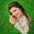Stock Photo: A smiling girl with yellow flowers