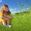 Dreaming girl in a fresh green grass — Stock Photo
