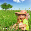 Dreaming girl sitting in the grass — Stock Photo