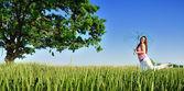 Mujer joven en un campo con paraguas — Foto de Stock