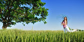 Young woman in a field with umbrella — Stock Photo