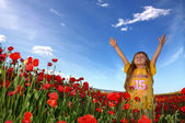 Little girl and field with poppy — Stok fotoğraf