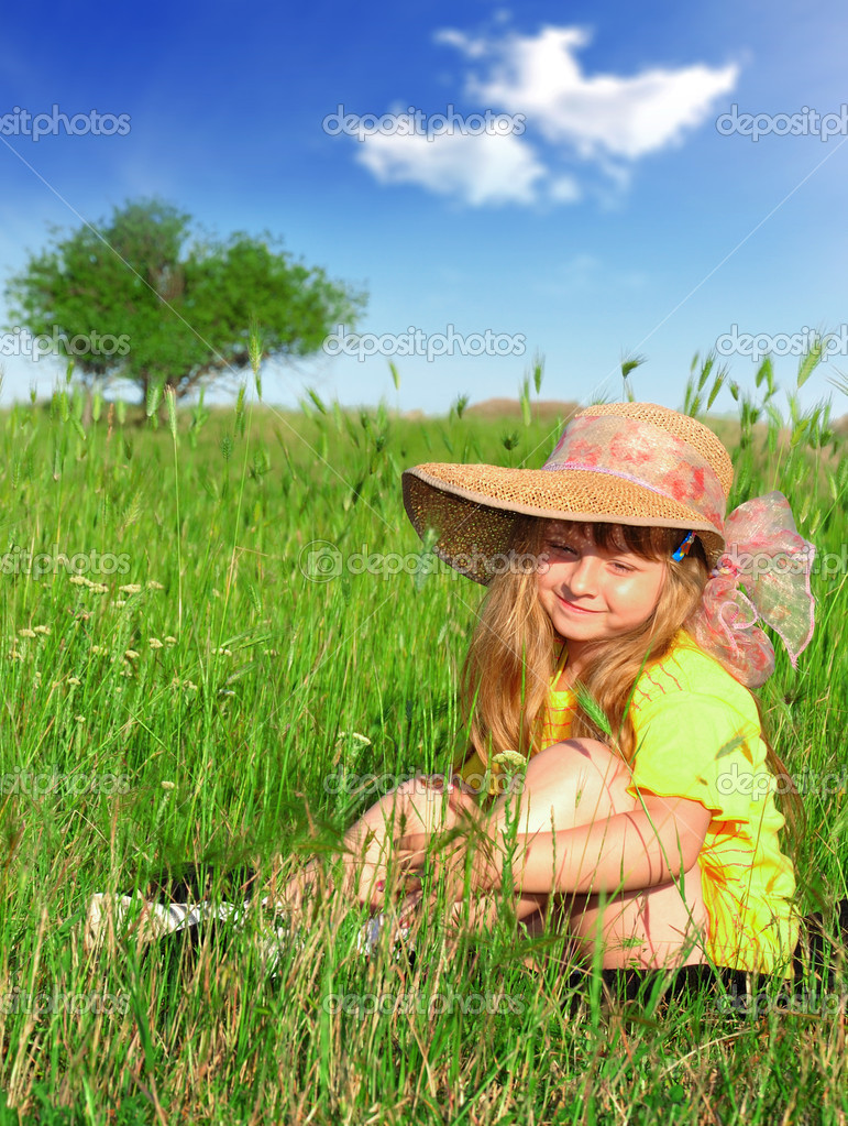 Little girl sitting and dreaming  on the grass — Stock Photo #2078523