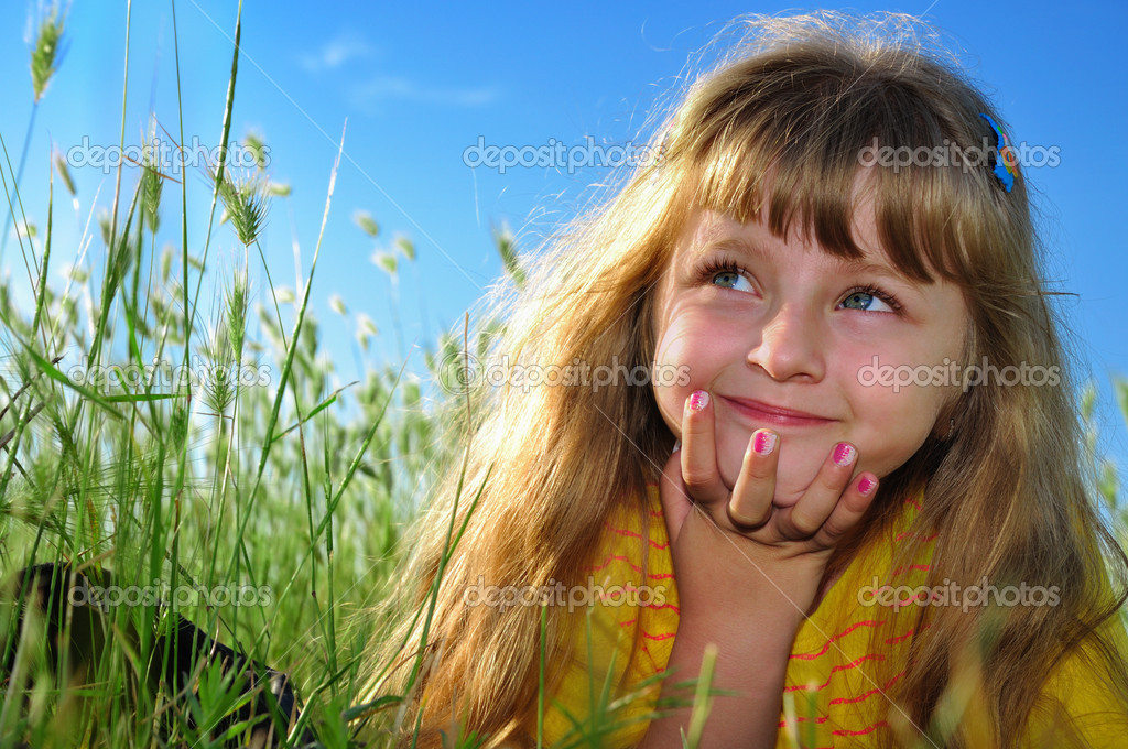 Little girl lying on the grass and dreaming — Stock Photo #2078539