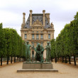 Bronze statue in front of Louvre museum — Stock Photo