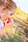 Little girl eating an apple — Stock Photo