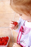 Little girl holding a raspberry — Stock Photo