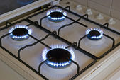 Four blue flames of a gas stove — Stock Photo