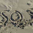 Stock Photo: SOS written in sand