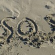 SOS written in sand — Stockfoto