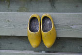 Clogs hanging on a fence — Stock Photo