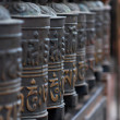 Buddhist prayer wheels in a row — Stockfoto
