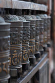 Buddhist prayer wheels in a row — Stock Photo