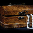 Chest with treasures isolated on black - Stock Photo