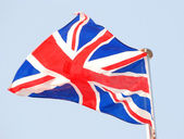 Great Britain flag against blue sky — Stock Photo