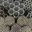 The round steel tubes of various size and caliber pile background. — Stock Photo #2479058