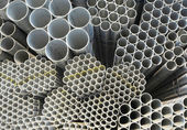 The round steel tubes of various size and caliber pile background. — Stock Photo