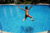 Boy jumping in swimming pool — Stock Photo