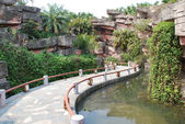 The wood board bridge in a water pond garden in a tropical resort China. — Stock Photo