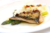 Sea bass with an asparagus and raisin — Stock Photo
