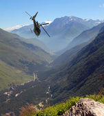 The helicopter flies in mountains — Stock Photo