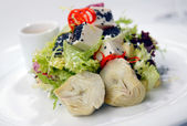 Salad with a crude and artichokes — Stock Photo