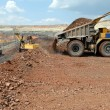 Dump-body truck unloading in mine - Stock Photo