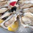 Oysters in ice with a lemon — Stock Photo