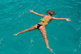 The girl lies on water in Caribbean sea — Stock Photo