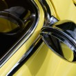 Reflected rearview mirror on yellow car — Stock Photo #2139130