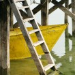 Yellow boat under the dock - Stock Photo