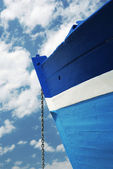 Chain of a white and blue wooden boat — Stock Photo