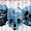 Blue skulls on earth - Stock Photo