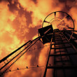 Refinery ladder under evil sky — Stock Photo