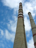 Two chimneys on the cloudy sky — Stock Photo