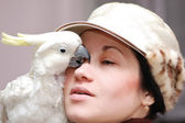 Girl with kissing parrot — Stock Photo