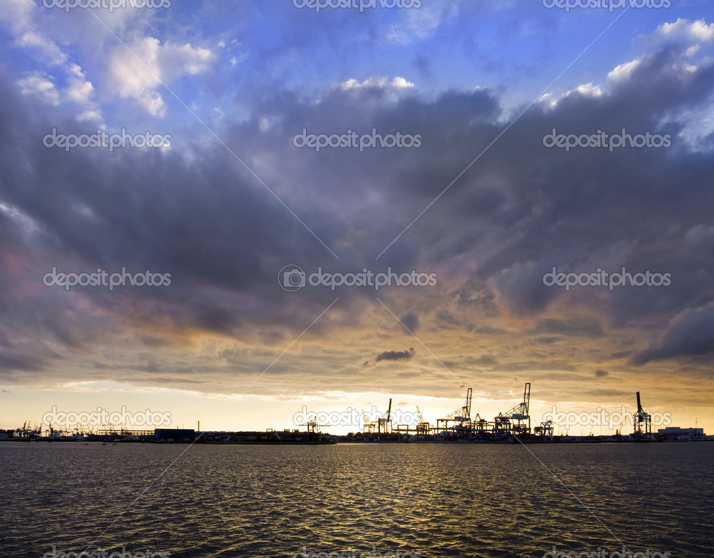 A fiery sunset with dramatic clouds over a commercial harbor in the distance — Stock Photo #2079094