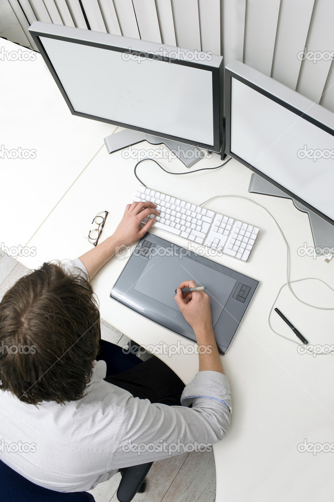 A designer working behind two monitors, using a keyboard and a graphic tablet  Stockfoto #2088228