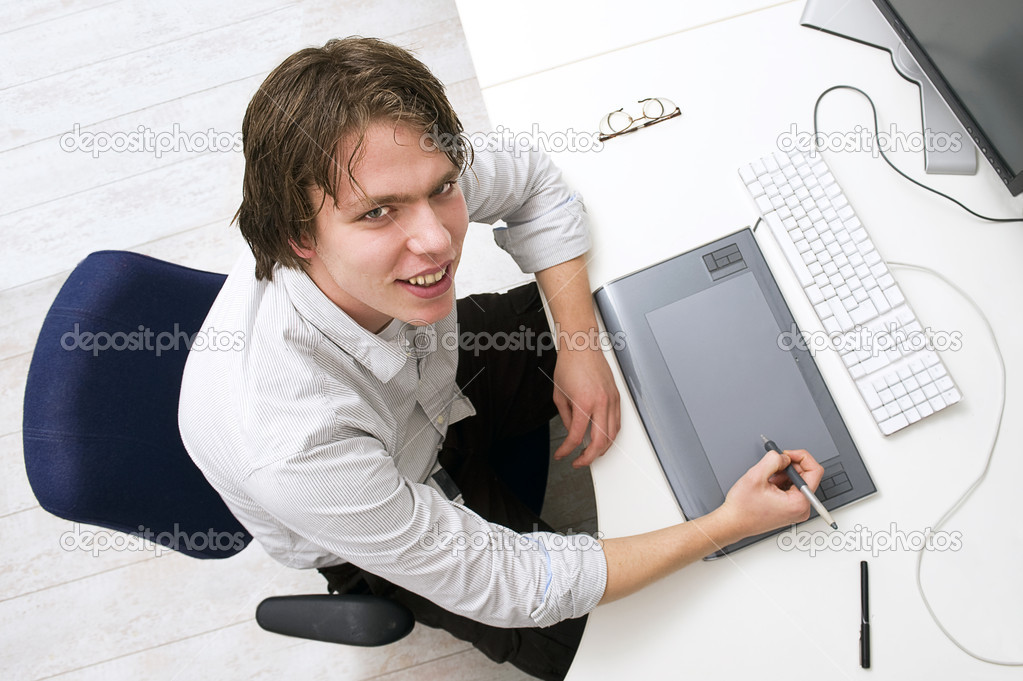 Portrait of a man sitting behin a desk with keyboard, graphic tablet and monitor in an office — Stock Photo #2088445