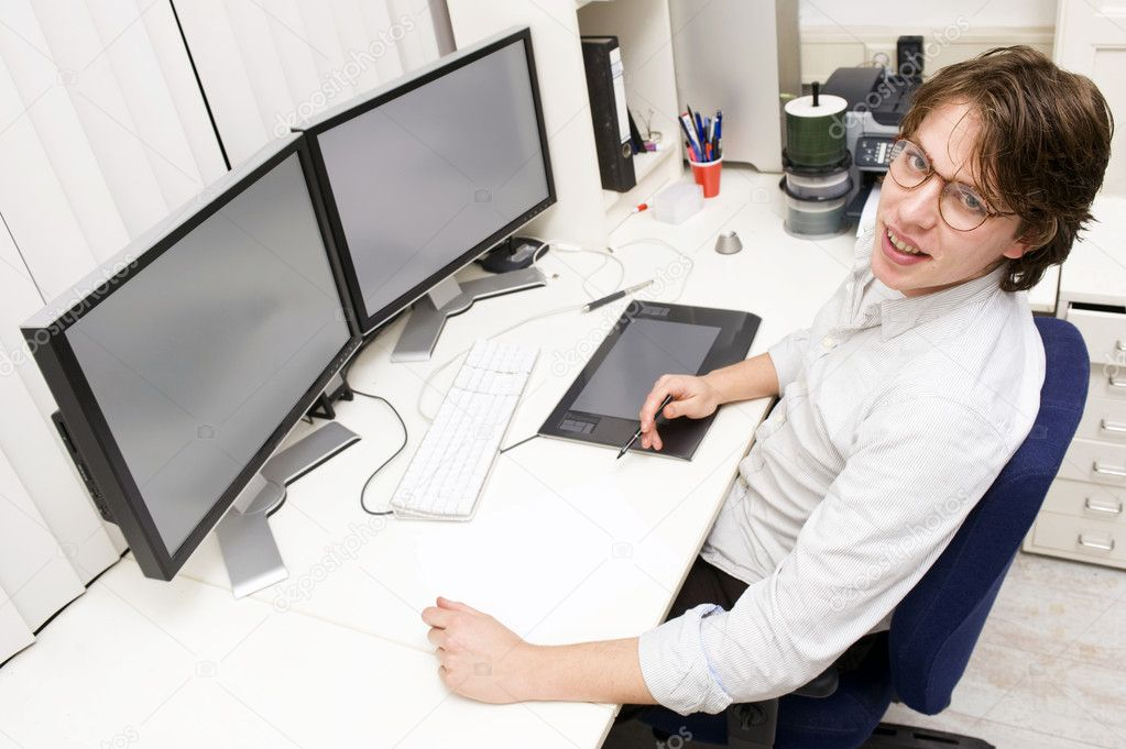 A designer at work behind two monitors, looking up at the camera — Stock Photo #2088527