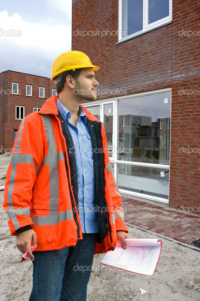 A building inspector visiting a construction site with a checklist in his hand  Stock Photo #2089259