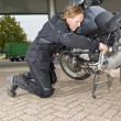 A motorcyclist checking his bike — Stock Photo