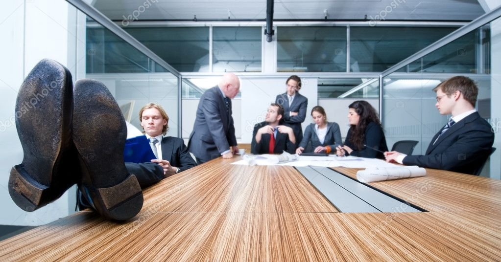 Young businessman, sitting with his feet resting on the table, obviously bored with what's happening in the meeting he's attending — Stock Photo #2098907