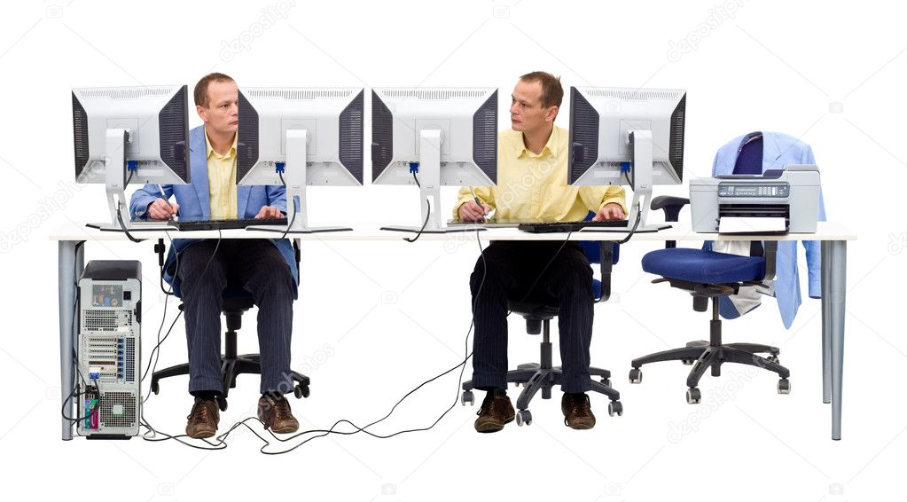 Two computer geeks working together behind a large desk, using several monitors — Stock Photo #2101098