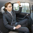 Businessman in a taxi - Stock Photo