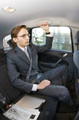 Businessman in a taxi — Stock Photo