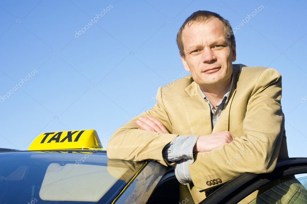 A taxi driver posing behind the front door of his cab  Stock Photo #2111112