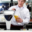 Foto Stock: Bartender tapping beer