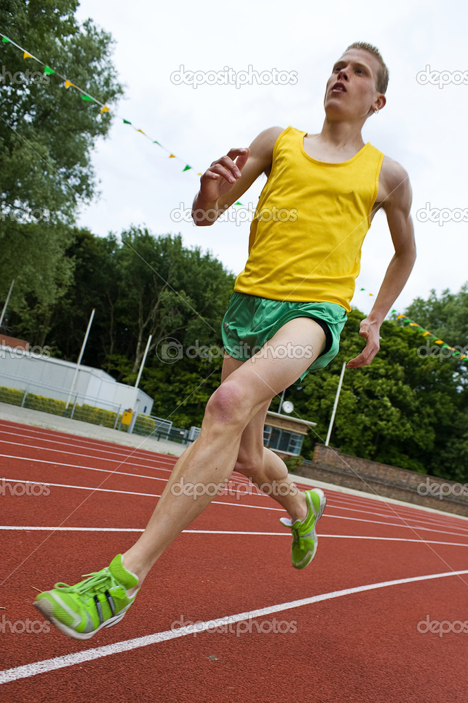 Running athlete on a middle distance race on an oval track in mid-air  Foto de Stock   #2136842